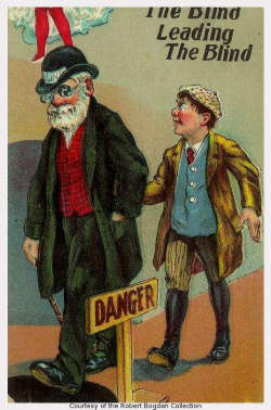An old blind man is leading a blind youth; Not seeing danger sign, both are about to fall into a man hole.